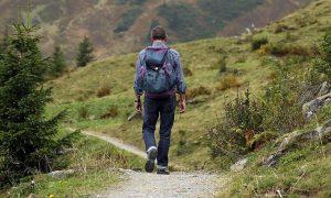 мъж в гръб върви в планината
