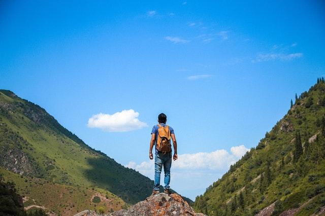 човек изкачващ планини