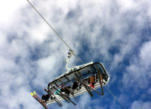 хора със ски оборудване в кабинков лифт