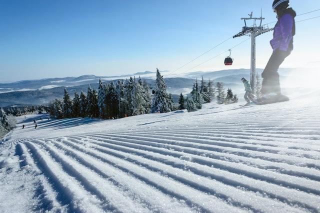 сноубордистка се спуска по писта