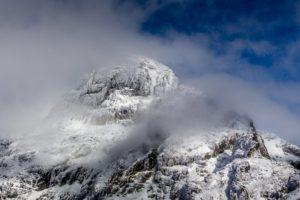 снежен планински връх обвит в облаци